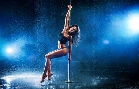 Photo pour Young sexy slim brunette woman pole dancing in dark interior with smoke and water - image libre de droit