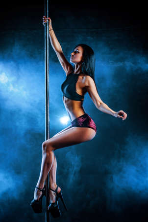 Photo pour Young sexy woman pole dancing on dark background with smoke - image libre de droit