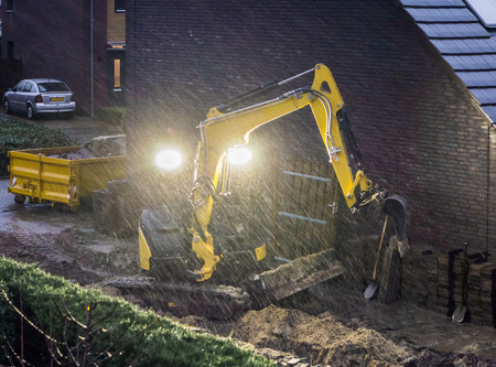 Photo pour ground worker working on a garden in bad rainy weather in the evening - image libre de droit