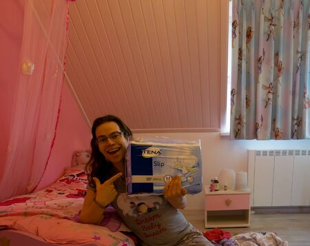 Foto de young person holding a package of Tena Ultima Confio Air, Medical Adult diapers, Popular brand for incontinence products - Imagen libre de derechos
