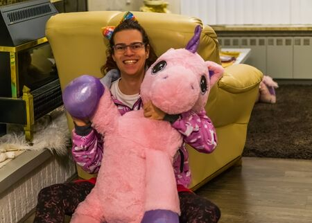 Photo for very funny and cute portrait of a transgender girl holding a stuffed unicorn and waving, LGBT Diversity - Royalty Free Image