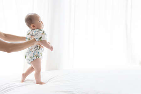 Photo pour Asian baby learning to walk for the first step on the soft bed - image libre de droit