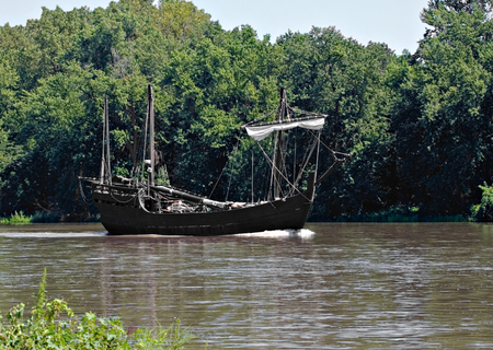 Old sail boat floating down a river