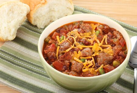 Bowl of chili with cheese on top with bread in background