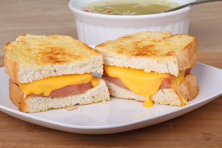 Grilled ham and cheese sandwich with soup in the background