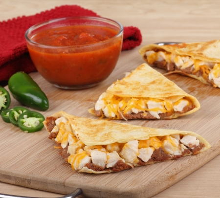 Chicken quesadillas cut into wedges with salsa and pepper on a cutting board