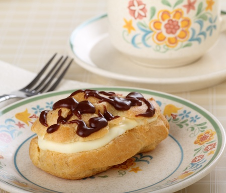 Cream filled eclair with chocolate on a plate