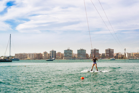 TORREVIEJA, SPAIN - SEPTEMBER 13, 2014: Cute girl learns to surf on background of yachts and boats in La Bocana, Cable Ski, Torrevieja, Marina Salinas. Valencia, Spain