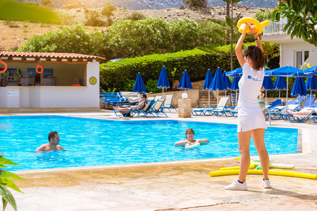 BALI, GREECE - APRIL 29, 2016: Animation at Resort hotel Atali Village 4 star. Cute girl in white beach suit conducts classes for tourists in water aerobics in pool with clean blue water.