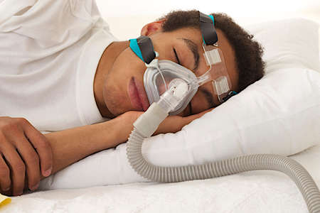 young mulatto man sleeping with apnea and CPAP machine: Royalty-free