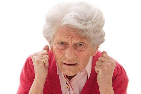 Foto de Angry old woman making fists on white background  - Imagen libre de derechos