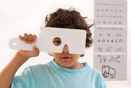 Young boy s eye exam HAVING Performed by optician, optometrist or eye doctor.