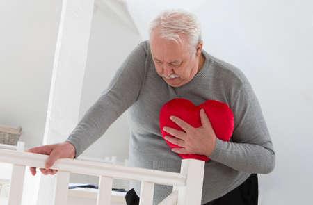 Photo pour Senior man holding an heart symbol of heart attack - image libre de droit