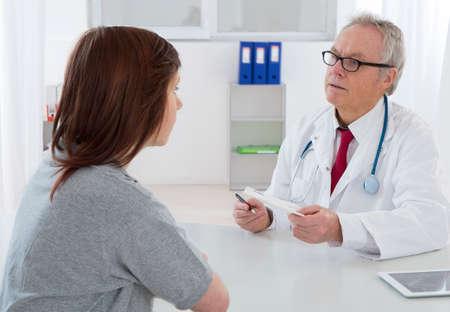 Photo pour Doctor talking to His young female patient at the office - image libre de droit