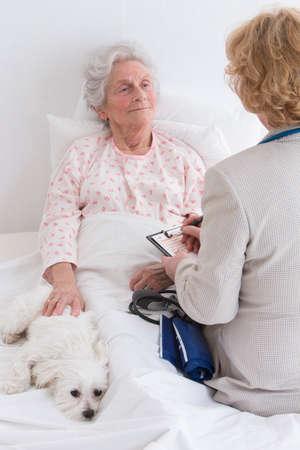 Photo pour female doctor visiting a senior patient. at home retierement house - image libre de droit