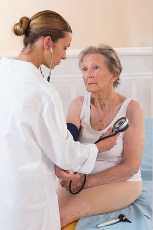 Photo pour Female doctor measuring blood pressure of senior woman - image libre de droit