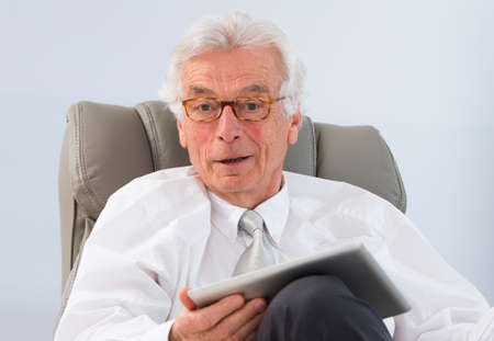 Photo pour Happy Senior Businessman Looking At Camera And Using Laptop At Workplace - image libre de droit