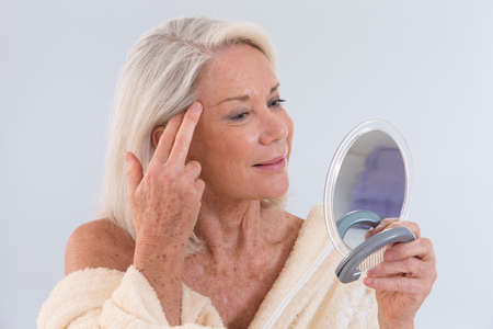 Mature woman looking at herself in the mirror showing her wrinklesの写真素材