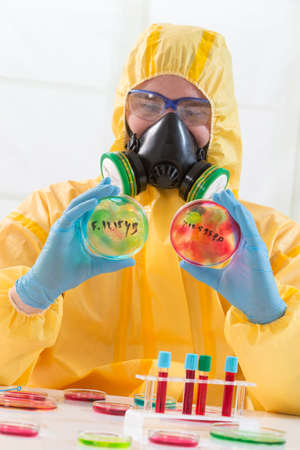 Scientist wearing protective suit and examining sample