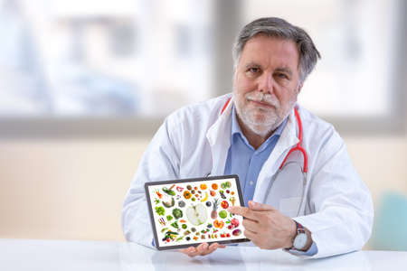 Photo pour Doctor nutritionist holdingb digital tablet.with vegetable and fruit on screen at office - image libre de droit