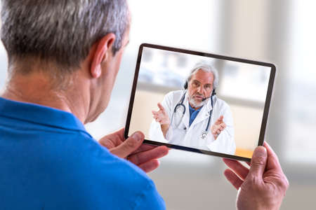 Photo for Telemedicine concept, Doctor sitting at hospital, with laptop, having an online call with a patient showing a ablet device - Royalty Free Image