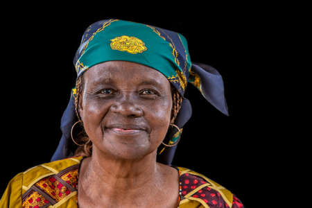 Photo pour Portrait of African senior citizen woman in her 70- with a happy face in gold and brown dress - image libre de droit