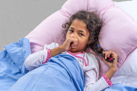 Photo pour Close portrate cute multiracial girl of 6-10 years old who is sucking her thumb in the bed - image libre de droit