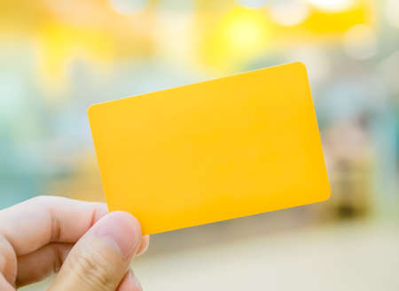 Hand holding yellow dummy card (to be replaced with your own) in the elegance atmosphere