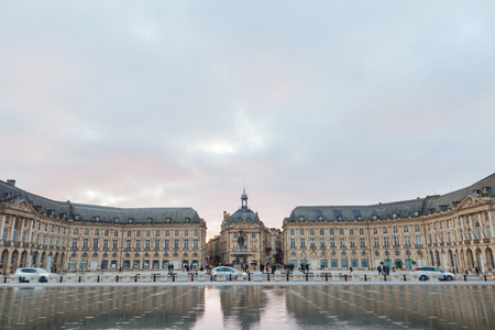 BORDEAUX, FRANCE - DECEMBER 24, 2017: Water Mirror (Miroir d'Eau) fountain on place de la Bourse square. It is one of the symbols of Bordeaux, and the biggest reflecting pool in the WorldPicture of Mirroir d'Eau (Water Mirror) in Bordeaux, France, on Pl