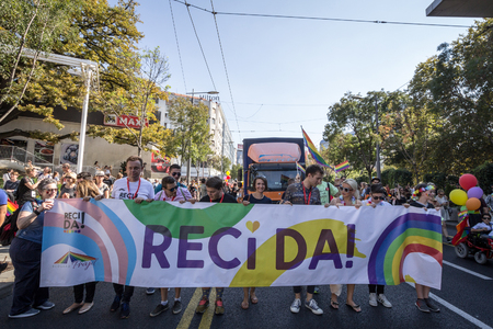 BELGRADE, SERBIA - SEPTEMBER 16, 2018:  Activists holding a banner in favor of same sex union and gay flags in the middle of the crowd during the Belgrade Gay Pride. The parade happened this year without troublePicture of LGBTQ activits holding a banner