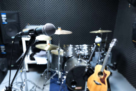 Photo for Professional condenser studio microphone, Musical Concept. recording, selective focus  microphone in radio studio, selective focus microphone and blur musical equipment guitar ,bass, drum piano background. - Royalty Free Image