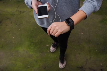 Foto de Young woman using wearable tech during fitness workout - Imagen libre de derechos