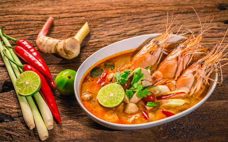Tom Yum Goong Thai hot spicy soup shrimp  with lemon grass,lemon,galangal on wooden background Thailand Food
