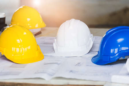 Photo pour The white, blue and yellow safety helmet stacking on table with the blueprint and measuring tools  at construction site for Engineer, foreman and worker. Safety first concept. - image libre de droit