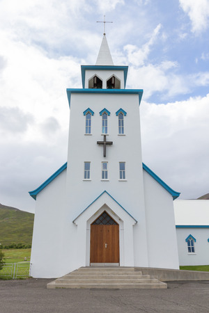 Typical small wooden church in front of a dramatic mountain backdrop in the fishing village of Dalvik, Iceland