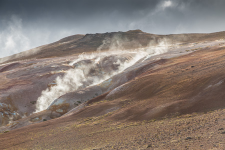 Steaming rim of a volcanic lava mountain in the Krafla region, Iceland