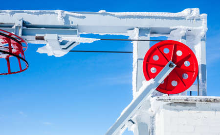 Ski lift red wheel elements on blue sky background