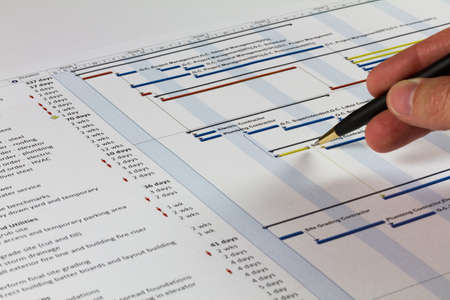 Photo pour Detailed Gantt Chart showing Tasks, Resources and Notes. Includes a pen being held by a man on the right. - image libre de droit