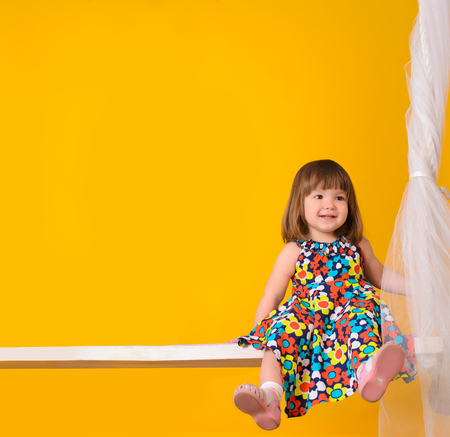 beautiful little girl sitting on the Swings, on a yellow background