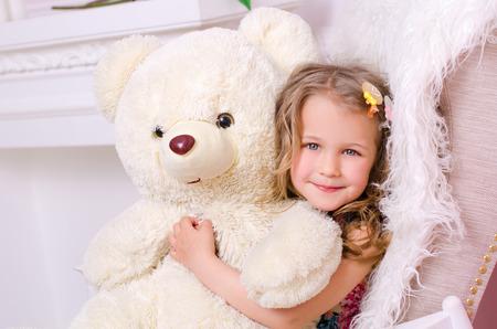 little cute girl embracing big white teddy bear indoors