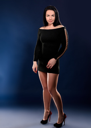 young tempting woman in black gown and high heel shoes on dark blue studio background