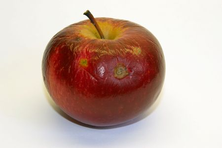 The red withered apple on a white background