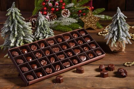 Photo pour Assortment of fine chocolate candies, white, dark, and milk chocolate sweets background. Christmas interior with gift boxes and Christmas fires - image libre de droit