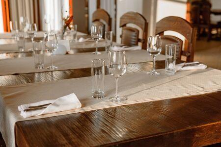 Photo pour Glasses, flower fork, knife served for dinner in restaurant with cozy interior. Empty glasses in restaurant - image libre de droit