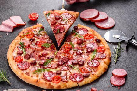 Photo pour Pepperoni Pizza with Mozzarella cheese, salami, ham. Italian pizza on a dark background - image libre de droit