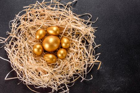 Photo for Easter golden eggs in the nest, preparation for the holiday. Golden eggs in nest on dark vintage background - Royalty Free Image