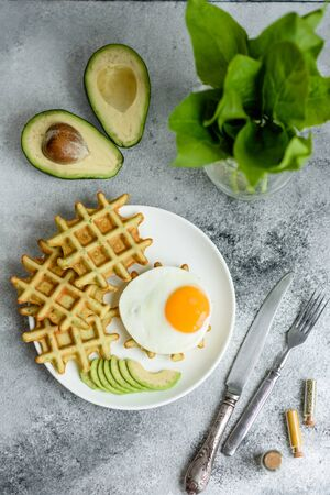 Foto für Fresh delicious and nutritious breakfast with waffles with spinach, fried egg and avocado pieces - Lizenzfreies Bild