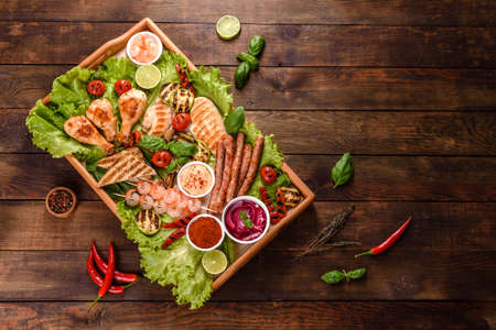 Photo pour Composition of sausages, chicken, pork and shrimp prepared on grill, as well as vegetables prepared on grill with spices and herbs. Cooking on fire - image libre de droit