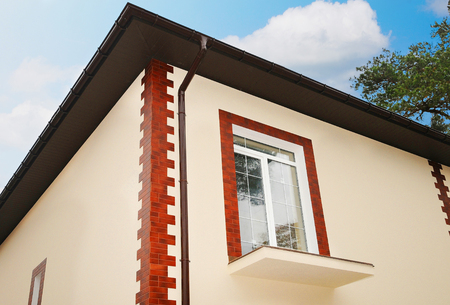 A new window in a new house. Unfinished balcony. Decorative plaster. Decorative tiles. roof construction. Urban house or building, facade pattern. Rain gutter