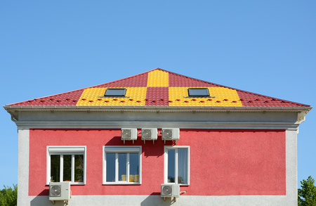 Metal roofing construction. House with a mansard and skylight. Rain gutter and snow guard. A multi-colored metal roof and many air conditioners.